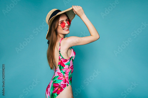 Fotografie, Obraz Beautiful lovely Sexy woman standing on blue background in  swimsuit or bikini and smiling while posing