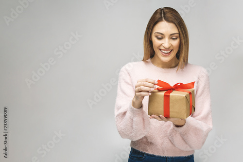 Image of Happy brunette woman in casual holding gift box and looking at the camera isolated over white background.