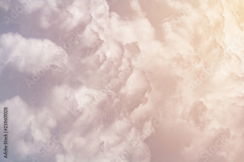 Fototapeta Cumulus fluffy clouds illuminated by orange sunlight  as background (abstract, t