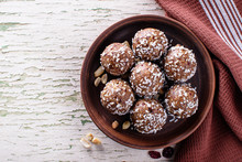 Raw Vegan Sweets, Energy Balls With Dried Fruits And Coconut. Brown Plate With A Napkin. Top View