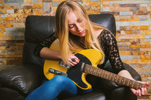 Young Musician Girl In Blue Jeans And Black Lace Shirt Sitting In Chair And Playing Guitar On Brick Background