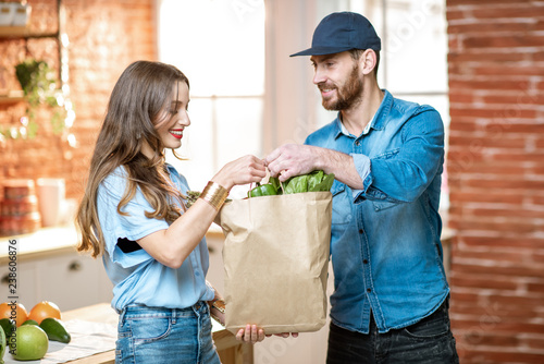 Fotografía  Courier service worker delivering fresh food, giving shopping bag to a happy wom