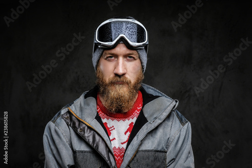 Photo Confident man with a red beard wearing a full equipment for extreme snowboarding, looking at a camera with a serious look, isolated on a dark textured background