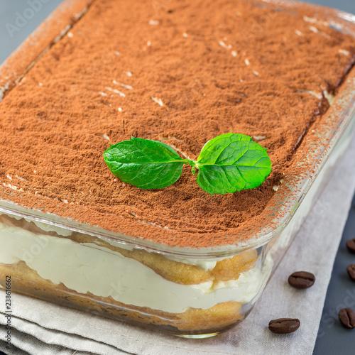 Fotografie, Obraz  Traditional italian Tiramisu dessert cake in a glass form, decorated with cocoa
