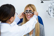 Woman optometrist with trial frame checking patient's vision at eye clinic. Selective focus on doctor.