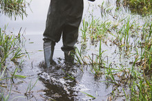 Legs In Rubber Boots In Water. Man's Hobby. Fishing. Rubber Boots For Fishing