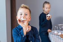 Siblings In A Kitchen Making Melted Snowman Cookies. Fun Craft Idea For All Ages.