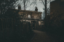 A Photo Of A Dark Scary Looking Haunted House In A Graveyard