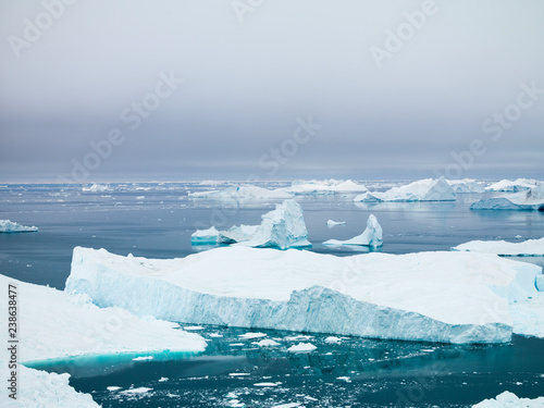 Papiers peints Arctique The glaciers are melting on arctic ocean in Greenland. Big glaciers day by day broking and dangerous for world climate system. Shooting day was foggy weather and glaciers didn't look clear.