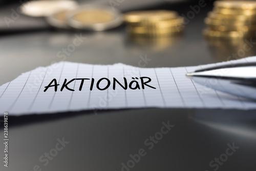 Fotografía  Aktionär auf einem Zettel mit Stift vor Geldmünzen