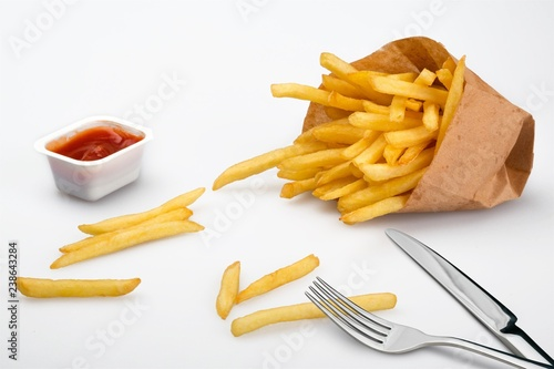 Paper box with pile of appetizing french fries over white planks
