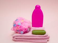 Set Of Woman Aroma Therapy Shower Preparing Equipment Like Towel, Puffy Sponge, Green Fruit Aroma Soap And Shampoo On Pink Background