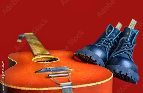 Rock and roll concept. Black boots and acoustic guitar. Rock and roll boots on claret background - 238662403