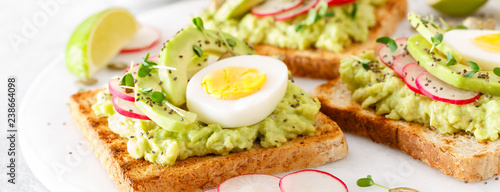 Fotografía  Toasts with avocado guacamole, fresh radish, boiled egg, chia and pumpkin seeds