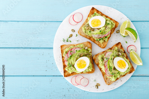 Fototapeta Toasts with avocado guacamole, fresh radish, boiled egg, chia and pumpkin seeds. Diet breakfast. Delicious and healthy plant-based food. Flat lay. Top view obraz