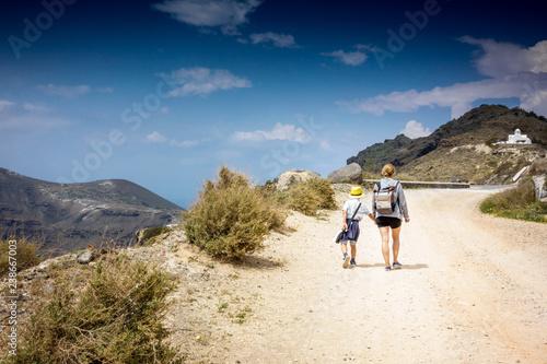 Fotografia, Obraz  Mother with son walking on dirt road leading to mountain; Santorini island; Gree