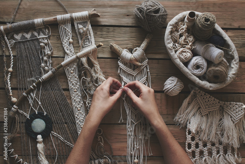 Photo  Female hands weaving macrame on a wooden table