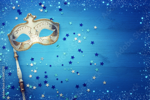 carnival party celebration concept with elegant gold mask on stick over blue wooden background and stars. Top view.