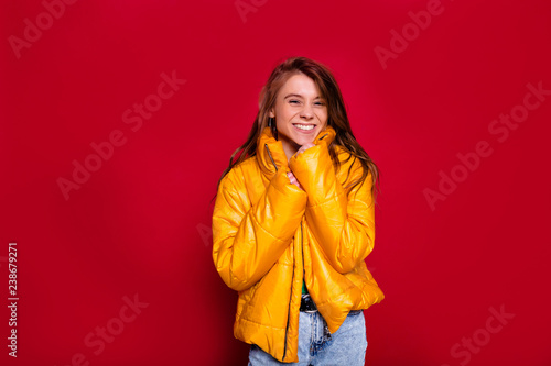 Adorable lovely happy girl with long hair wearing bright yellow winter jacket posing while photoshoot on red background. Pleased girl wears jeans laughing on claret background - 238679271