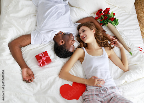 Poster Hoogte schaal Valentine's Day. happy couple with red hert and flowers in bed