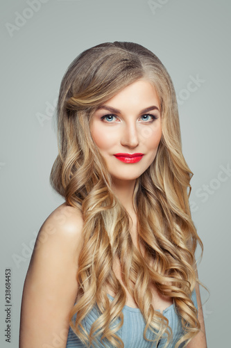 Beautiful blonde woman portrait. Elegant female model with long healthy curly hair and red lips makeup