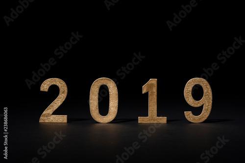 Fotografía  Año nuevo en números de madera 2019, color dorado sobre fondo negro