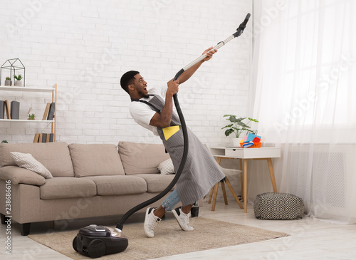 Fotografie, Obraz  Young man cleaning house with vacuum cleaner