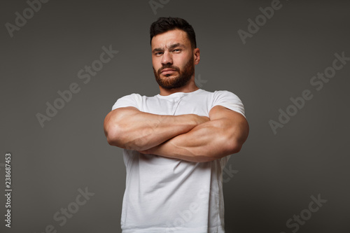 Photo Suspicious young man with crossed big muscular arms