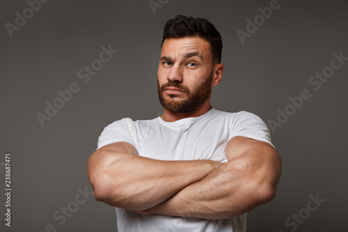 Suspicious young man with crossed big muscular arms Canvas Print