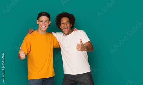 Obraz Teenage friends showing thumbs up over blue background - fototapety do salonu