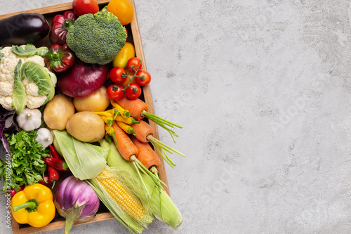 Valokuvatapetti Fresh organic vegetables in wooden box on gray