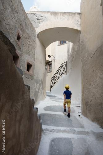 Fotografia  Little boy walking in narrow residential alley; Santorini island; Greece