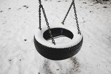 Old Abandoned Set Of Tire Swings Covered By Snow Against Winter Forest Landscape Background. Childhood Memories Concept.