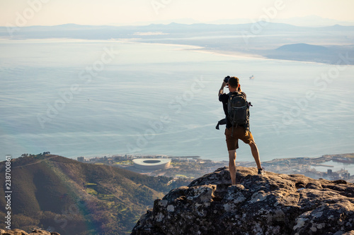 Fotografie, Obraz A man is taking a picture on top of the table mountain