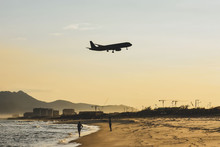 Airplane Silhouette On Bright Sunny Cloudy Sky Background. Landing At The Airport By The Sea