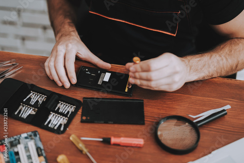 Fototapeta Close up Young Man Repairing Mobile Phone at Table obraz