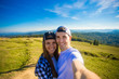 Young couple hiking taking selfie with smart phone. Happy young man and woman taking self portrait with mountain scenery