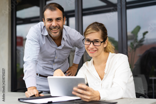 Fototapeta Portrait of happy business colleagues with digital tablet looking at camera and smiling. Young Caucasian woman wearing glasses sitting at table and mid adult man standing by. Team concept obraz na płótnie