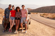Young adult friends on a road trip take a break by their car