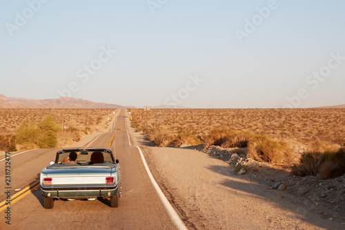Photo  Couple driving convertible car on desert highway, back view