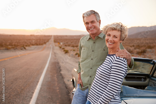 Fotografía  Senior couple on road trip standing by car smiling to camera