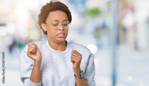 Fotografie, Obraz  Young beautiful african american woman wearing glasses over isolated background disgusted expression, displeased and fearful doing disgust face because aversion reaction