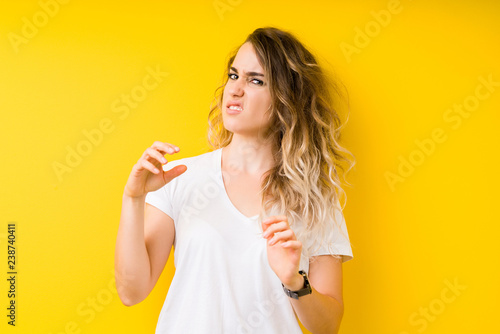 Fotografie, Tablou  Young beautiful blonde woman over yellow background disgusted expression, displeased and fearful doing disgust face because aversion reaction