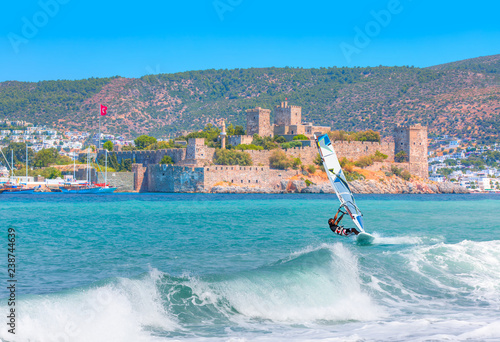 Saint Peter Castle (Bodrum castle) and marina in Bodrum, Turkey - Beautiful cloudy sky with Windsurfer Surfing The Wind On Waves