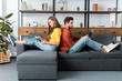 young smiling woman with notebook sitting back to back on sofa with man using laptop