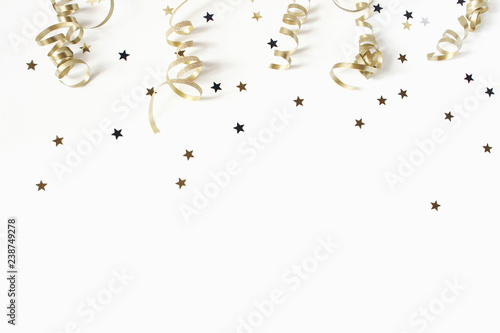 Happy New Year or birthday festive composition. Golden confetti and glittering stars on white table background. Celebration, party concept. Flat lay, top view. Empty copy space.