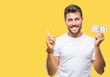 Young handsome man holding dollars over isolated background very happy pointing with hand and finger to the side