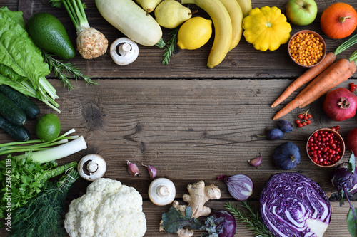 Fototapeta  White, yellow, green, orange, red, purple fruits and vegetables on wooden background