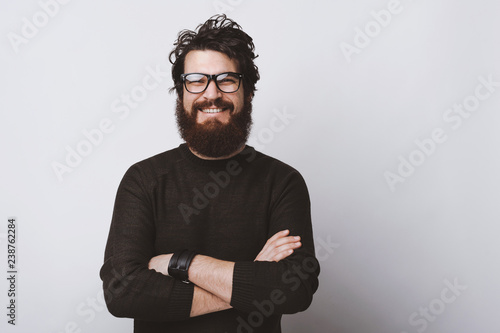 Fotografija Happy smart handsome young man wearing glasses and smiling at camera crossing arms on white background