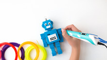 A Child, Teen Boy Makes A Plastic Robot, Draws Its Parts With A 3D Pen. STEM And STEAM Education. Development, Modeling, Design And Programming Of The Robot. Modern Technologies. DIY.